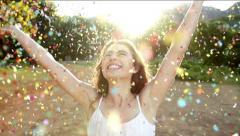 Young Woman throwing confetti in the park in slow motion Stock Footage
