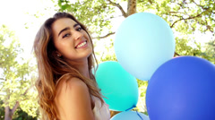 Girl enjoying summer's day with balloons in the park - stock footage