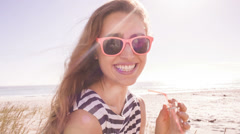 Smiling girl with lemonade at the beach - stock footage