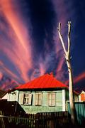 Abandoned green wooden house with red roof - stock photo