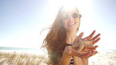 Smiling girl showing starfish at the beach Stock Footage