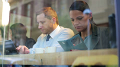 Businesspeople work on laptop and use cellphone in cafe, steadycam shot. - stock footage