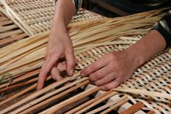 hands mastering wicker fabric - stock photo
