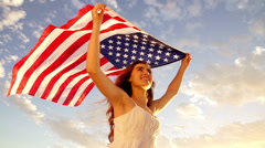 american woman holding stars and stripes against sky - stock footage
