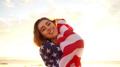 Woman wrapped in star and stripes on the beach Stock Footage