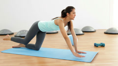 Fit brunette doing pilates on exercise mat Stock Footage