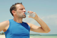 Stock Video Footage of Male jogger drinking water after workout on the beach NTSC