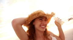 Woman with drink and straw hat dancing on the beach Stock Footage