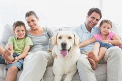 Happy family sitting on couch with their pet labrador - stock photo