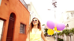 Smiling young woman walking with helium balloons - stock footage