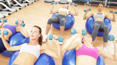 Fitness class lying on exercise balls lifting hand weights Stock Footage