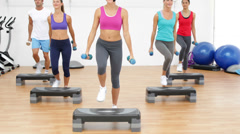 Aerobics class stepping together led by instructor and lifting dumbbells Stock Footage