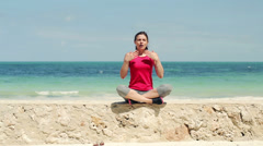 Beautiful woman doing breathing exercise on the wall by the sea HD Stock Footage