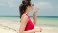 Stock Video Footage of Attractive female jogger drinking water on the beach HD