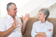 Stock Photo of Senior couple sitting on couch having an argument