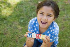 Stock Photo of Happy girl holding block alphabets as 'play' at park