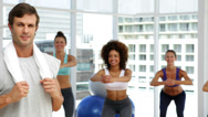 Stock Video Footage of Fitness class squatting on bosu balls while instructor smiles at camera