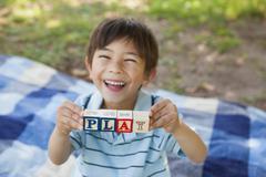 Happy boy holding block alphabets as 'play' at park - stock photo