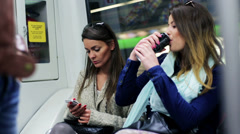 Women in subway using cellphone drinking and talking, steadycam shot. Stock Footage