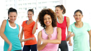 Stock Video Footage of Pretty instructor leading zumba class in fitness studio