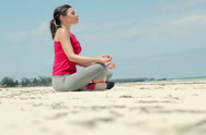 Stock Video Footage of Young woman meditating on the beach NTSC