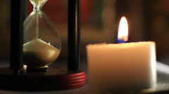 Burning candle near a hourglass Stock Footage