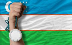 Stock Photo of silver medal for sport and  national flag of uzbekistan