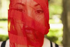 A young woman with a red see-through sheer veil across her face. - stock photo