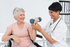 Physiotherapist assisting senior woman to lift dumbbell Stock Photos