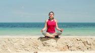Stock Video Footage of Young beautiful woman meditating by the sea HD