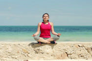 Stock Video Footage of Young beautiful woman meditating by the sea NTSC