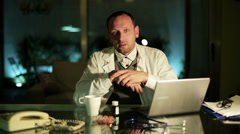 Doctor talking to camera at night in office. Stock Footage