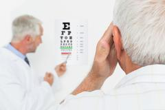 Pediatrician ophthalmologist with senior patient pointing at eye chart - stock photo