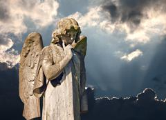 winged angel statue in graveyard - stock photo