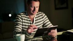 Happy man using tablet at night by the table. Stock Footage