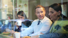 Businesspeople drinking coffee in cafe and talk, steadycam shot. Stock Footage