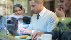 Businesspeople eating lunch and working on laptop in cafe, steadycam shot. Stock Footage
