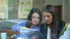 Businesspeople work on tablet and talk on cellphone in cafe, steadycam shot. - stock footage