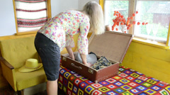Blond woman girl pack her clothes into retro travel suitcase Stock Footage