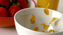 Cereal pouring into a bowl at breakfast table - stock footage