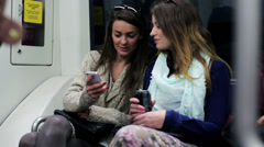 Women travel by subway and using cellphone, steadycam shot. - stock footage