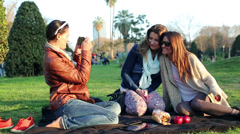 Happy women taking photo old camera and sitting in park, steadycam shot. Stock Footage