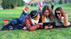 Happy women lying on blanket in park watch tablet and eat apple, steadycam shot. - stock footage