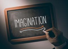 Stock Photo of Hand writing Imagination on chalkboard