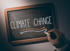 Hand writing Climate change on chalkboard Stock Photos