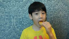 Little Asian child eating donut sweet food Stock Footage