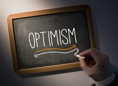 Hand writing Optimism on chalkboard - stock photo