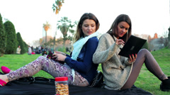 Women sitting in park back using tablet and talking. Stock Footage