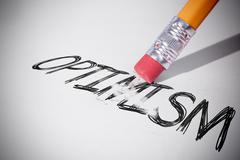 Pencil erasing the word Optimism - stock photo