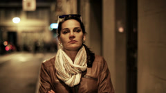 Pensive woman walking at night on street, steadycam shot. - stock footage